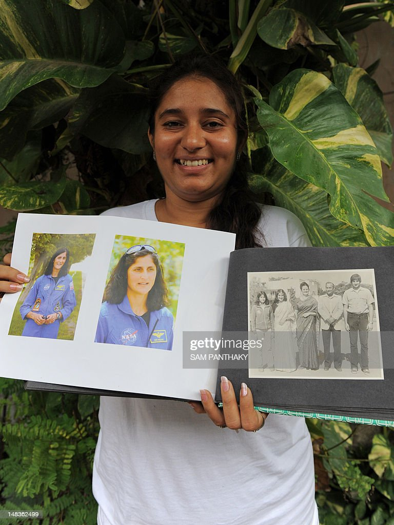 Vacha Pandya, niece of US astronaut of Indian-Slovenian origin Sunita Williams, holds a family photograph taken in 1976 and recent portraits of Williams, in Ahmedabad on July 15, 2012. A Russian rocket carrying an international crew of Akihiko Hoshide of Japan, Yuri Malenchenko of Russia and Sunita Williams of the US blasted off without a hitch on July 15 for the International Space Station in the first manned mission in two months. AFP PHOTO / Sam PANTHAKY