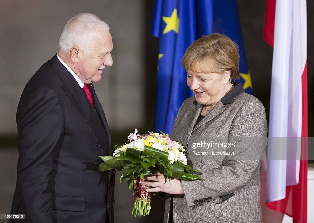 Vaclav Klaus president of the Czech Republic hands over flowers to German Chancellor Angela Merkel when he arrives at the Chancellery on January 9...