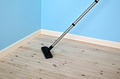 Vacuum cleaning bare wooden floorboards in empty room