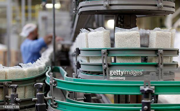 Vacuumpacked bags of white rice travel along a conveyor belt towards the packaging area inside Riso Scotti SpA's factory in Pavia Italy on Monday...