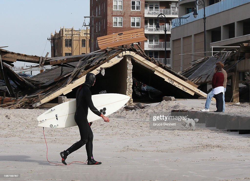 Vadim Zabreed walks past the damaged boardwalk prior to surfing on November 20, 2012 in Long Beach, New York. More than three weeks after Superstorm Sandy hit the New York area, residents continue their restoration efforts in many affected areas on Long Island.