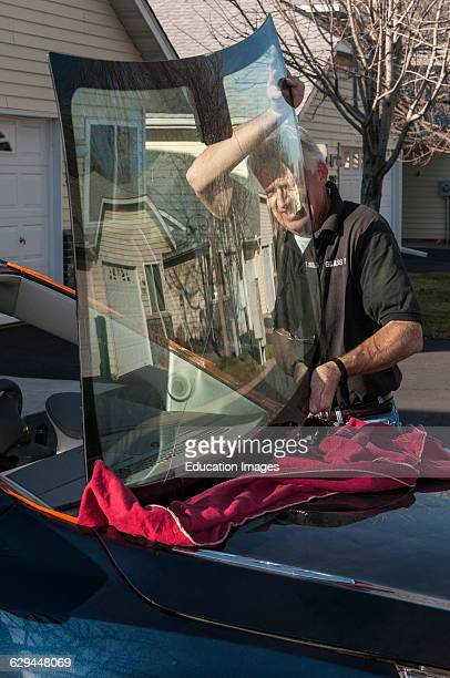 Vadnais Heights Minnesota A small business mobile glass service owner installing a new windshield on a new car Removing the old windshield