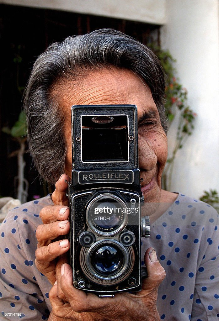Indian photographer Homai Vyarawalla poses with her Rolleiflex camera at her home in Vadodara, 06 March 2006. Ninety-three year old Homai lays claim to the title of India's first female photojournalist. Starting her career in the 1930's- with her parents permission and after finishing her studies - by assisting Maneksha, a photographer from the British Ministry of Information, whom she later married. She had her first publication in the 'Bombay Chronicle' in 1939 for which she was paid one Indian Rupee. Publications such as Time-Life used her post independence images of politicians including Nehru, Ho Chi Minh and other events of historical importance including the crossing into India from Tibet of H.H.The Dalai Lama in 1959.UNESCO recently published a book of her work which was launched in New Delhi. International Women's Day will be celebrated across the world 08 March. AFP PHOTO/STR