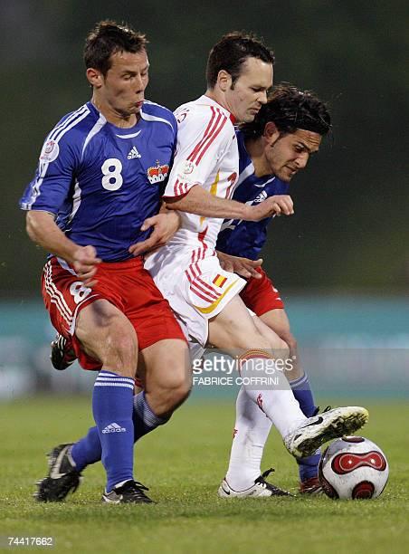 Liechtenstein's Ronny Buechel and teammate Liechtenstein's Michele Polverino vies with Spain's Andres Iniesta during their EURO 2008 qualifiying...