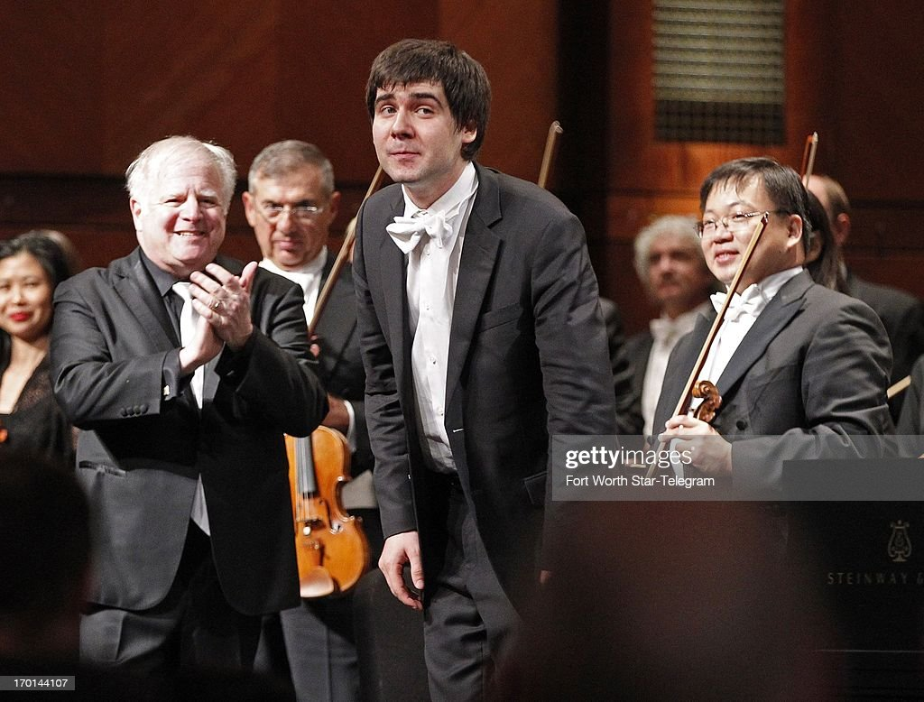 Vadym Kholodenko, of the Ukraine takes his bows as conductor Leonard Slatkin, left, and concertmaster Michael Shih look on, after his concerto with the Fort Worth Symphony Orchestra on the second day of finals in the 14th Van Cliburn International Piano Competition at Bass Performance Hall in Fort Worth, Texas, Friday, June 7, 2013.