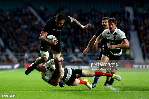 Vaea Fifita of New Zealand avoids a tackle from Andy Ellis of the Barbarians during the Killik Cup match between Barbarians and New Zealand at...