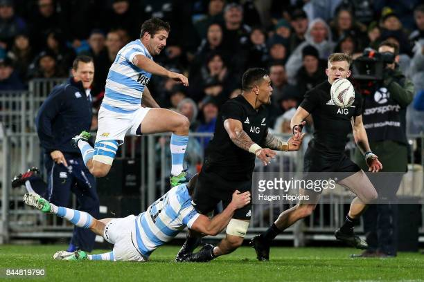 Vaea Fifita of New Zealand offloads to Damian McKenzie in the tackle of Emiliano Boffelli of Argentina during The Rugby Championship match between...