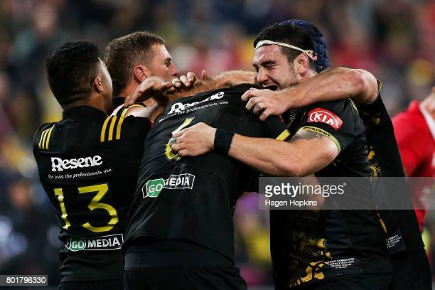 Vaea Fifita of the Hurricanes celebrates his try with Vince Aso Callum Gibbins and Jeff To'omagaAllen during the match between the Hurricanes and the...