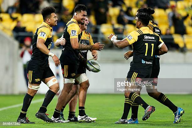Vaea Fifita of the Hurricanes is congratulated on his try by teammates Ardie Savea Reggie Goodes Julian Savea and Michael Fatialofa during the round...