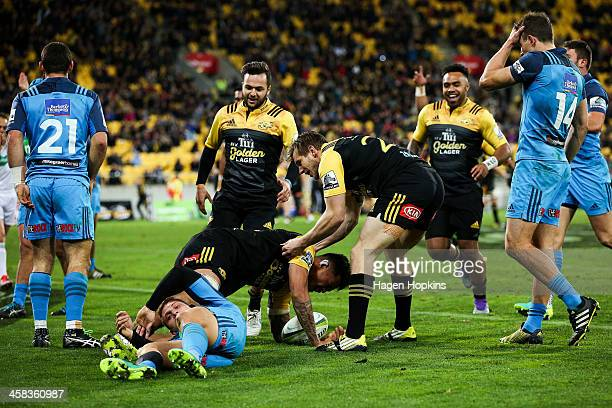 Vaea Fifita of the Hurricanes is congratulated on his try by teammates Jamison GibsonPark and Jason Woodward during the round 15 Super Rugby match...