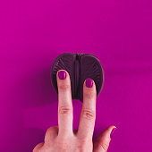 Vagina symbol. Two fingers on chocolate orange on purple background. Minimalism concept. Top view, copy space, square