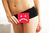 Vaginal or urinary infection and problems concept. Young woman holds paper with sad smile above crotch.