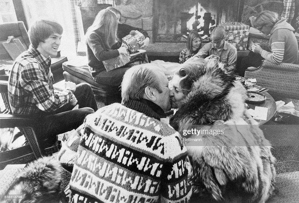 President Ford kisses his wife Betty while the Ford family opens Christmas gifts near the fireplace background December 25 Left to right Jack Ford 22...