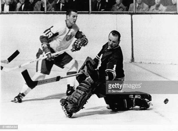 Val Fonteyne of the Detroit Red Wings watches the puck as goalie Johnny Bower of the Toronto Maple Leafs tries to make the save during the early...
