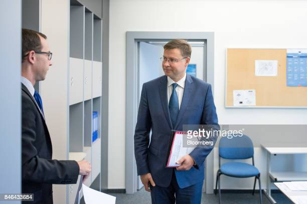 Valdis Dombrovskis vice president of the European Commission right speaks with an aide ahead of attending the State of the Union speech at the...