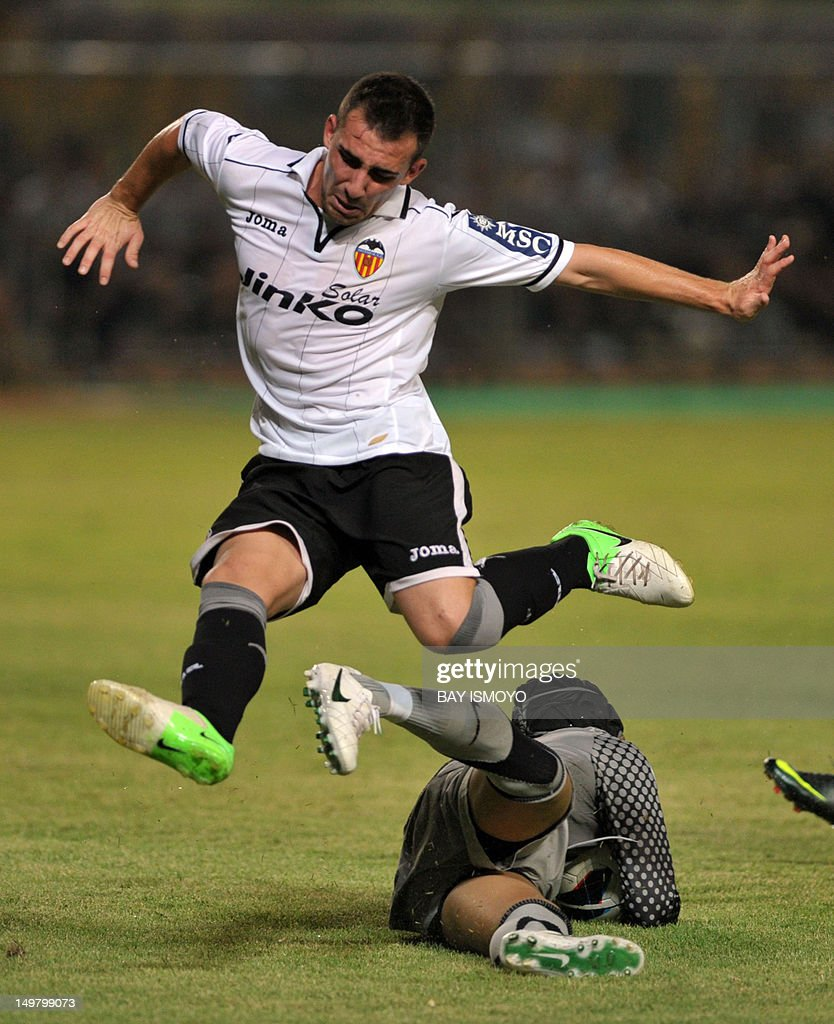 Valencia CF's Francisco Alcacer plows past Indonesian goalkeeper Wahyu Tri Nugroho (L) during a friendly football match between Spain's Valencia CF and Indonesia at the Bung Karno stadium in Jakarta on August 4, 2012. AFP PHOTO / Bay ISMOYO