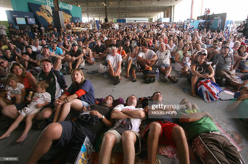 Spectators watch the race on a big screen at the America's Cup port in Valencia 24 June 2007 Challenger Emirates Team New Zealand beat Swiss defender...