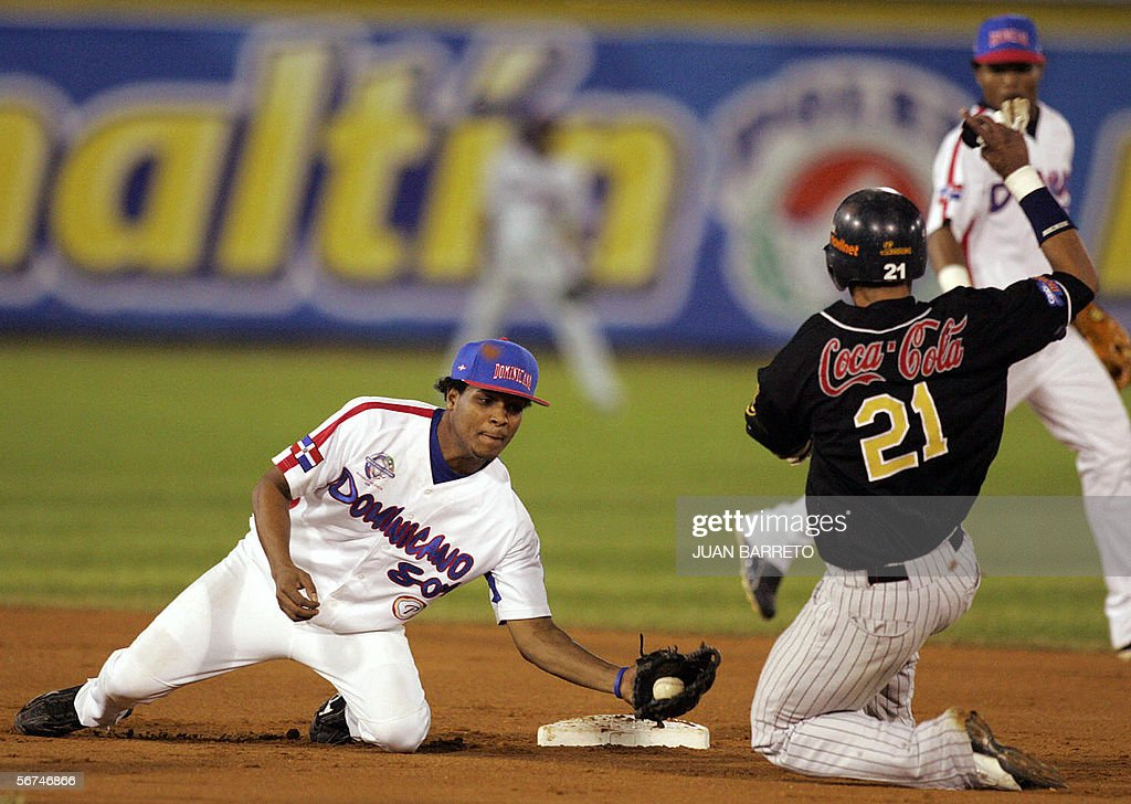 Franklin Gutierrez of Leones of Caracas slides into second base as Anderson Hernandez of the Tigres Licey of the Dominican Republic attempts to tag...