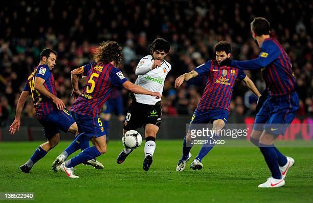 Valencia's Argentinian midfielder Ever Banega vies with Barcelona's Argentinian midfielder Javier Mascherano Barcelona's captain Carles Puyol...