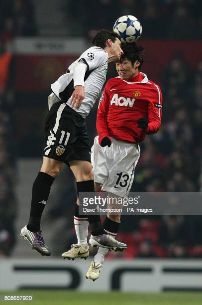 Valencia's Aritz Aduriz and Manchester United's JiSung Park battle for the ball in the air