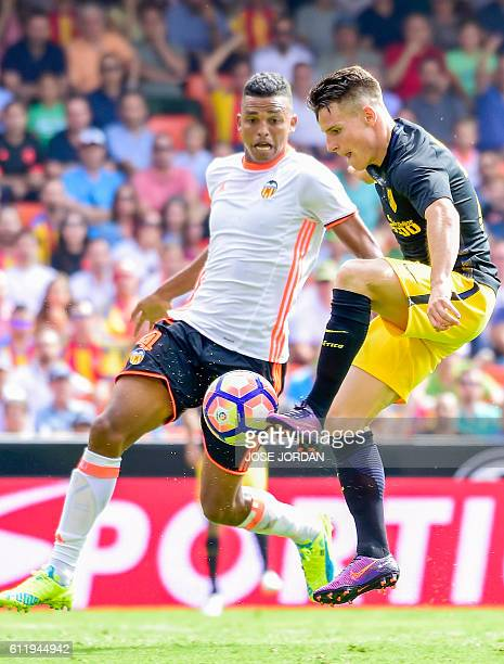 Valencia's Brazilian defender Aderlan Leandro de Jesus Santos vies with Atletico Madrid's French forward Kevin Gameiro during the Spanish league...