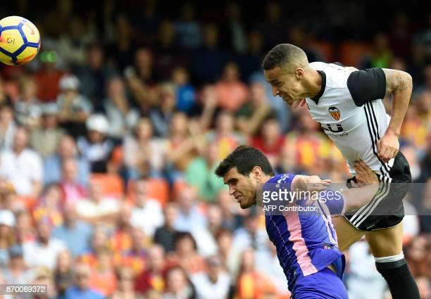 Valencia's Brazilian forward Rodrigo Moreno heads the ball beside Leganes' Argentinian defender Ezequiel Munoz to score a goal during the Spanish...