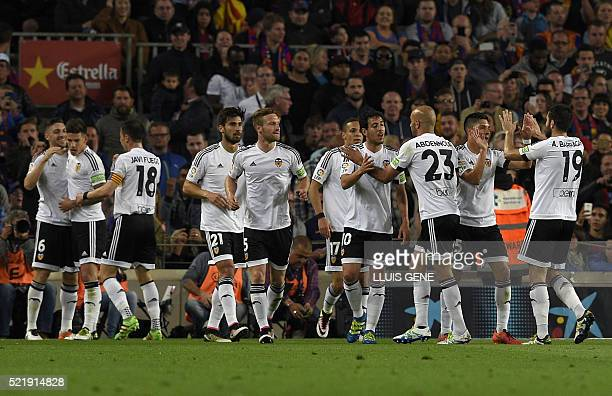 Valencia's Brazilian midfielder Guilherme Siqueira celebrates with teammates after scoring a goal during the Spanish league football match FC...