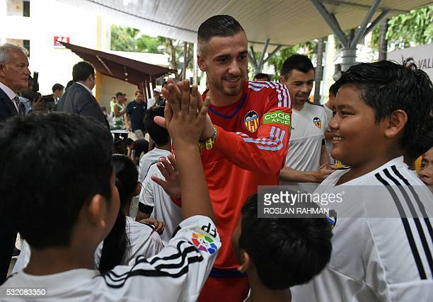 Valencia's CF Spanish footballer Jaume Domenech highfives children during a neighbourhood youth community event at Bukit Ho Swee in Singapore on May...