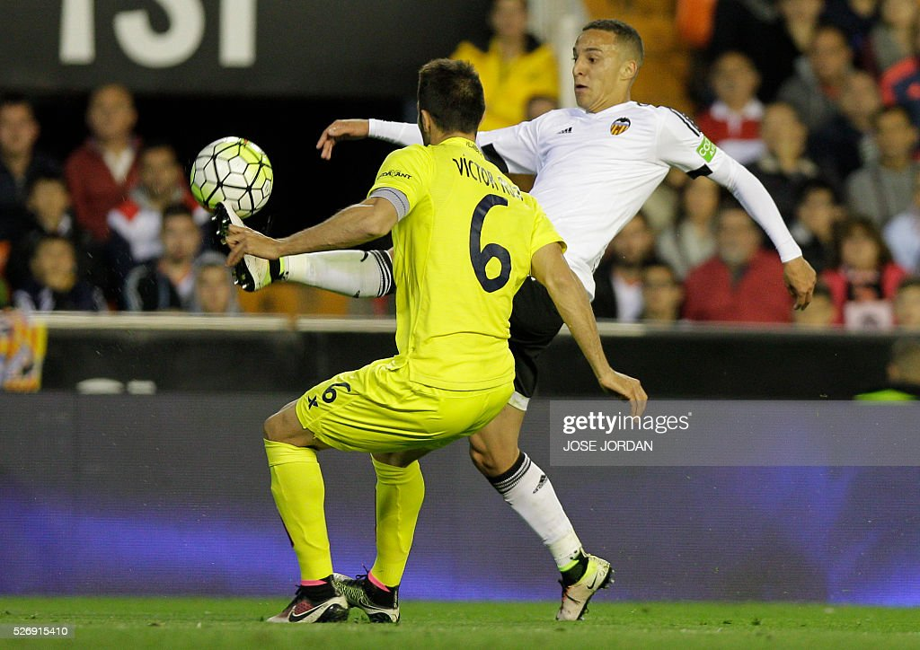 Valencia's forward Rodrigo (R) controls the ball during the Spanish league football match Valencia CF vs Villarreal CF at the Mestalla stadium in Valencia on May 1, 2016. / AFP / JOSE