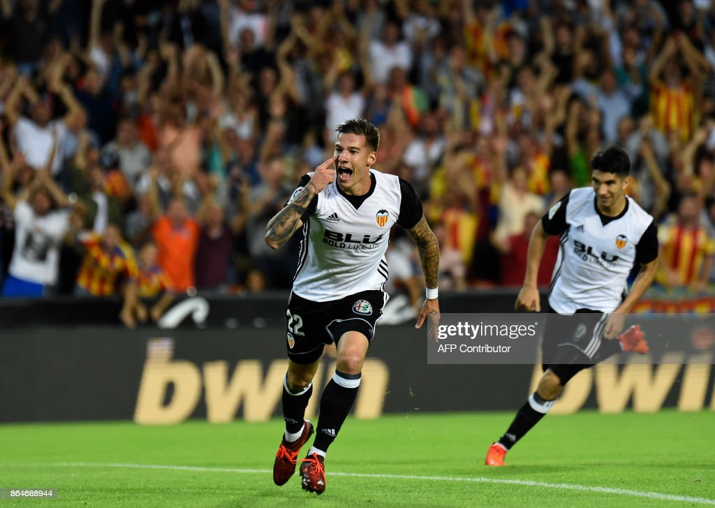 Valencia's forward Santi Mina (L) celebrates after scoring a goal during the Spanish league football match Valencia CF vs Sevilla FC at the Mestalla stadium in Valencia on October 21, 2017. /