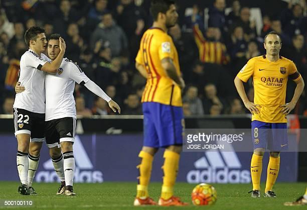 Valencia's forward Santi Mina celebrates his goal with Valencia's forward Paco Alcacer as they walk past Barcelona's midfielder Andres Iniesta during...