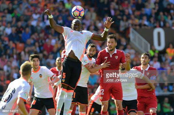 Valencia's French defender Eliaquim Mangala heads the ball beside Sevilla's Italain midfielder Franco Vazquez during the Spanish league football...