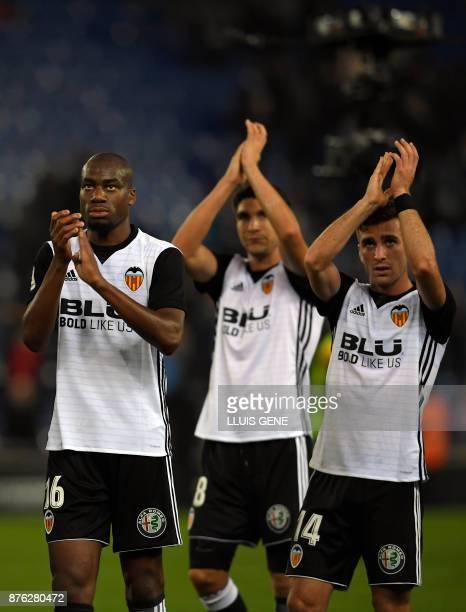 Valencia's French midfielder Geoffrey Kondogbia applauds with Valencia's Spanish midfielder Carlos Soler and Valencia's Spanish defender Jose Luis...