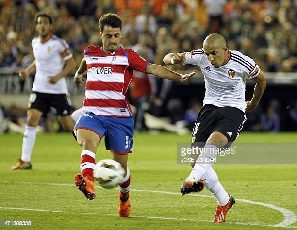 Valencia's French midfielder Sofiane Feghouli shoots to score a goal next to Granada's Portuguese defender Luis Carlos Ramos Martins during the...