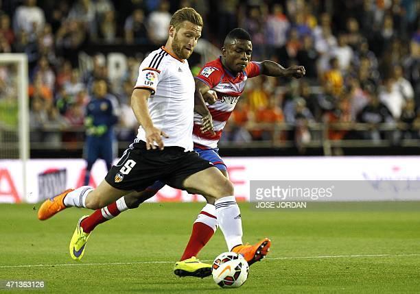 Valencia's German defender Shkodran Mustafi vies with Granada's Colombian forward Jhon Cordoba during the Spanish league football match Valencia CF...