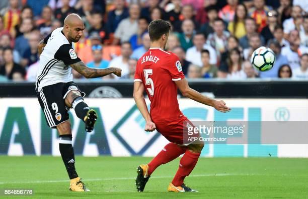 Valencia's Italian forward Simone Zaza challenges Sevilla's French defender Clement Lenglet during the Spanish league football match Valencia CF vs...
