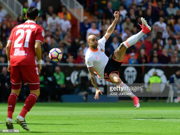 Valencia's Italian forward Simone Zaza jumps to kick the ball during the Spanish league football match Valencia CF vs Sevilla FC at the Mestalla...