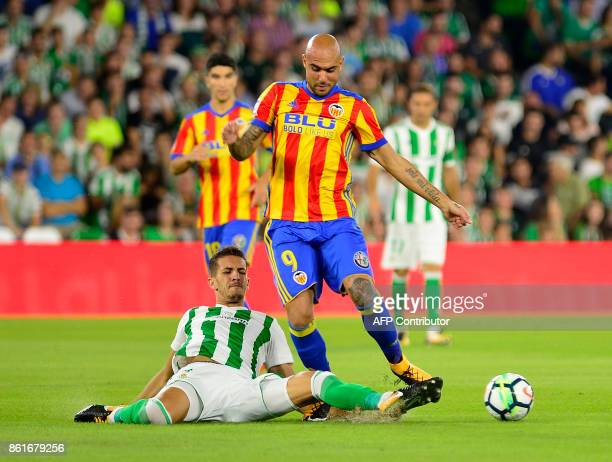 Valencia's Italian forward Simone Zaza vies with Real Betis' Moroccan defender Zou during the Spanish league football match Real Betis FC vs Valencia...