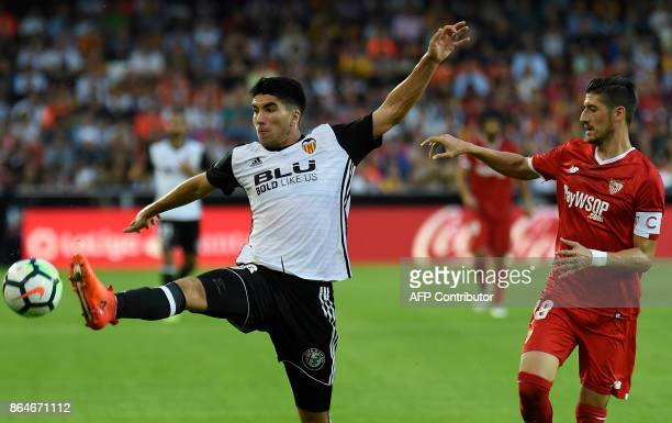 Valencia's midfielder Carlos Soler challenges Sevilla's defender Sergio Escudero during the Spanish league football match Valencia CF vs Sevilla FC...