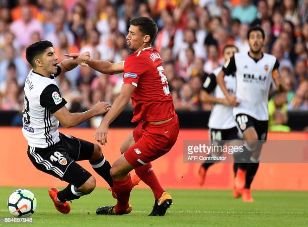Valencia's midfielder Carlos Soler challenges Sevilla's French defender Clement Lenglet during the Spanish league football match Valencia CF vs...
