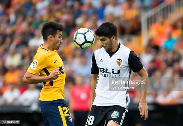 Valencia's midfielder from Spain Carlos Soler vies with Atletico Madrid's midfielder from Argentina Nico Gaitan during the Spanish Liga football...