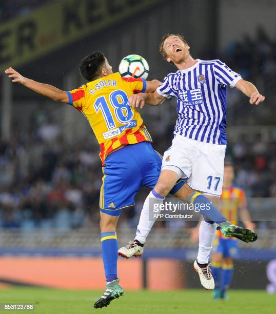 Valencia's midfielder from Spain Carlos Soler vies with Real Sociedad's midfielder from Spain David Zurutuza during the Spanish league football match...