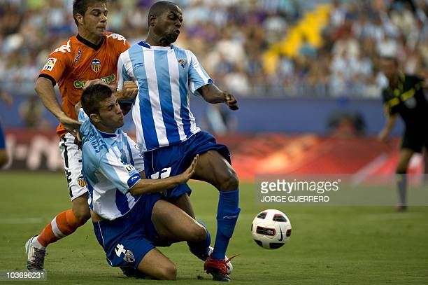 Valencia's midfielder Joaquin Sanchez Rodriguez vies with Malaga's Manu Torres and Brazilian Sandro Silva during a Spanish league football match at...