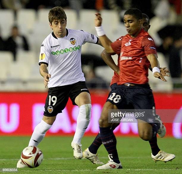 Valencia's midfielder Pablo Hernandez figths for the ball with Lille's Frank Beria during their Europe league football match at Mestalla Stadium in...