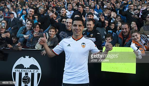 Valencia's new signing Argentinian midfieler Enzo Perez poses infront of football fans during his official presentation at the Mestalla stadium in...