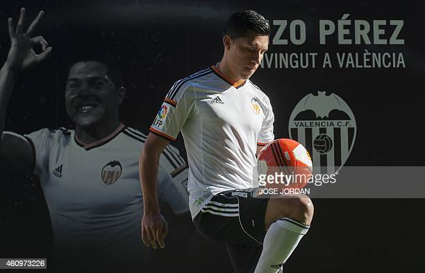 Valencia's new signing Argentinian midfieler Enzo Perez poses with a ball during his official presentation at the Mestalla stadium in Valencia on...