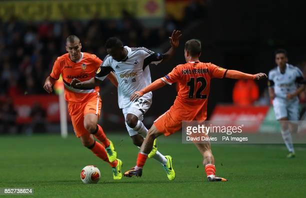Valencia's Pedro Joao Pereira and Swansea City's Roland Lamah battle for the ball
