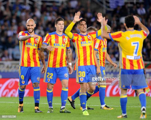 Valencia's players celebrate after forward from Italy Simone Zaza scored his team's third goal during the Spanish league football match Real Sociedad...