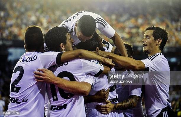 Valencia's players celebrate their goal during the Spanish league football match Valencia CF vs Granada CF at the Mestalla stadium in Valencia on...
