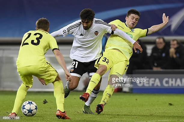 Valencia's Portuguese midfielder Andre Gomes vies for the ball with Ghent's Danish defender Lasse Nielsen and Ghent's Belgian midfielder Thomas Foket...